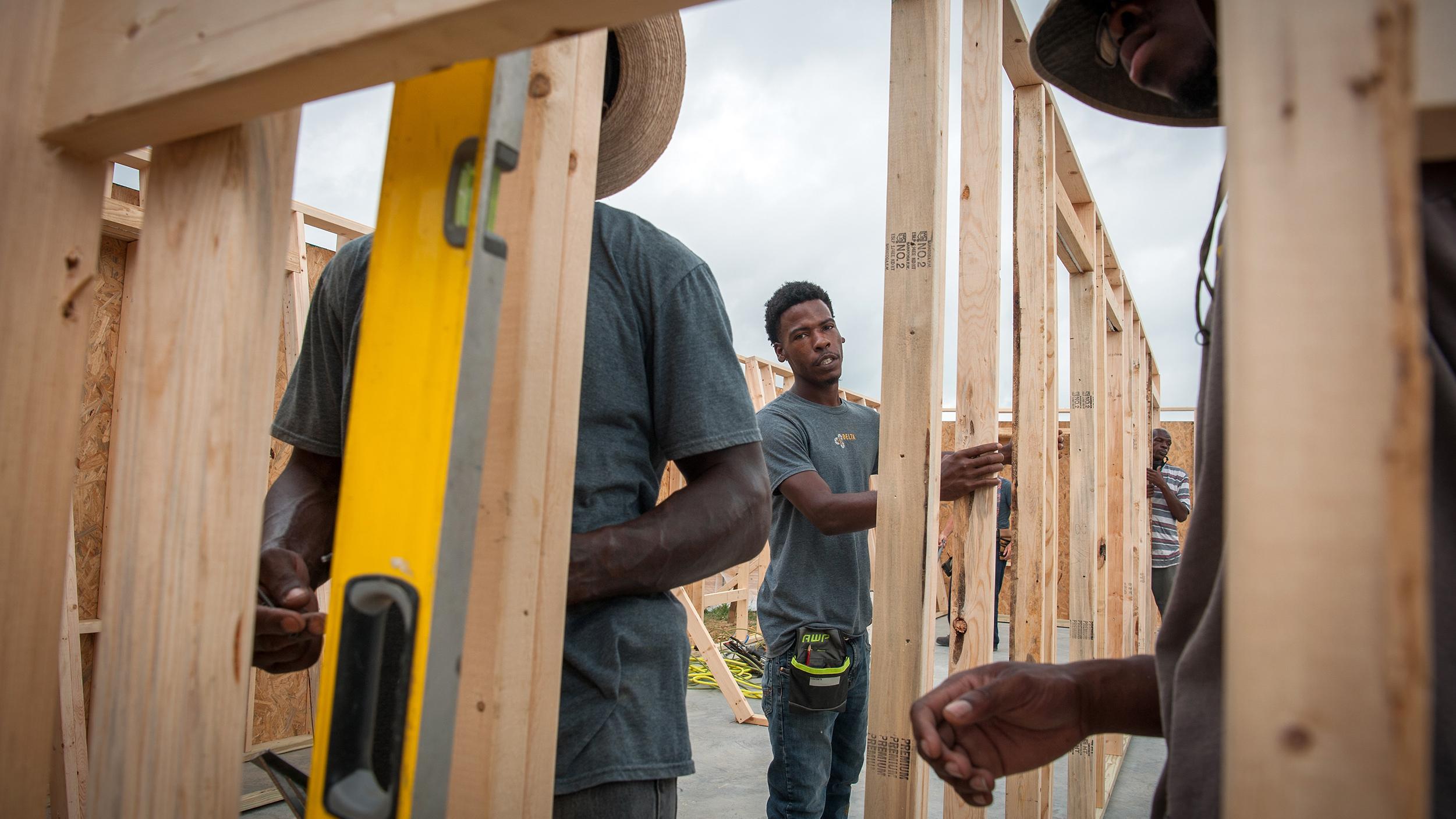 BJ Kinds (center), construction manager with Delta Design Build Workshop, frames a house in Eastmoor on Sept. 2, 2020.