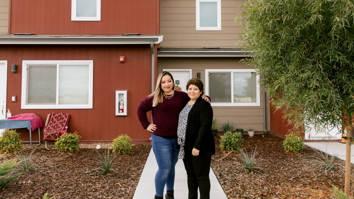 Portrait of Claudia Miranda and her mother, Martha Baltazar, in front of Martha's home at Rosaleda Village in Wasco, Calif.