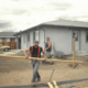 A family works on their self-help home in El Milagro. Courtesy of CRHDC.